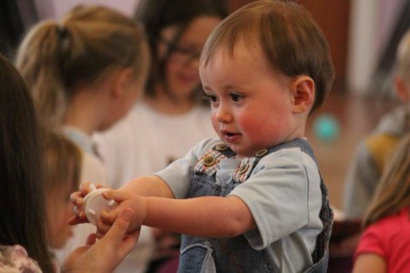 Ein Kind einer Kindergartengruppe übergibt einem anderen Kind ein Spielzeug.